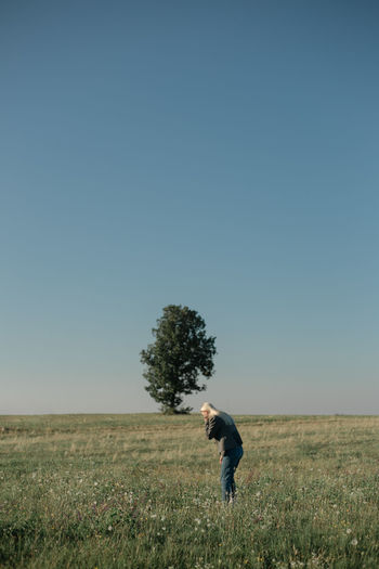 Side view of woman standing on field against clear sky