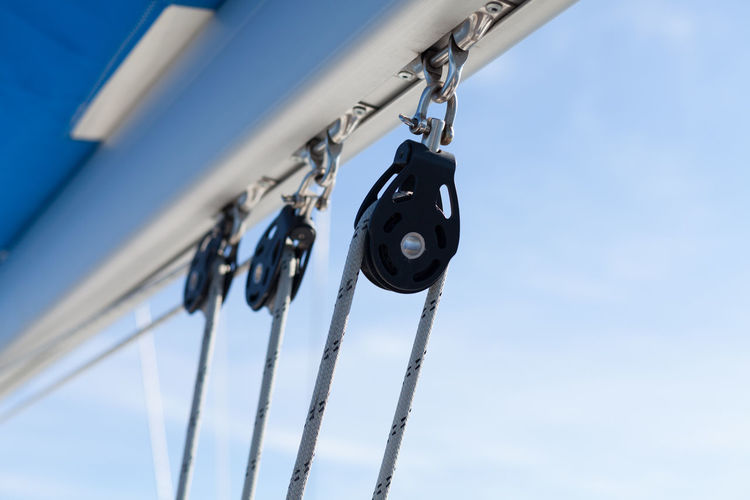 Low Angle View Of Ropes On Pulleys Against Sky