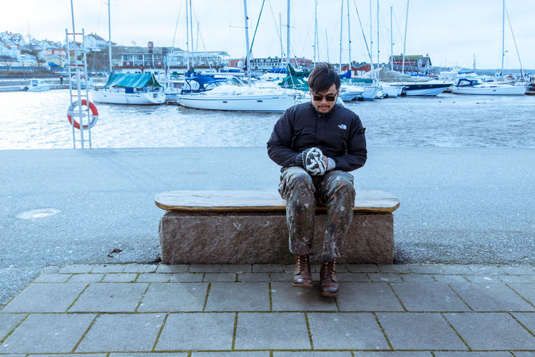 Full length of man sitting at harbor