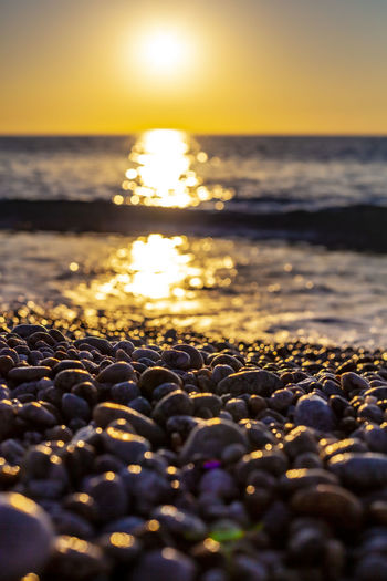View of stones at beach during sunset