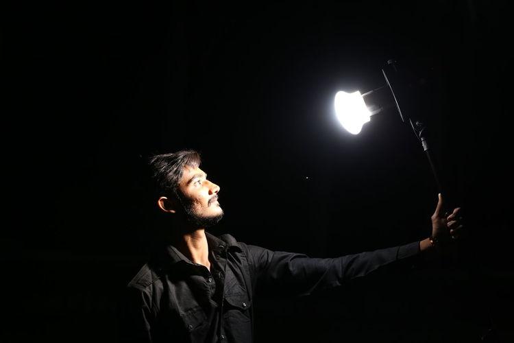 Man looking at illuminated light against black background
