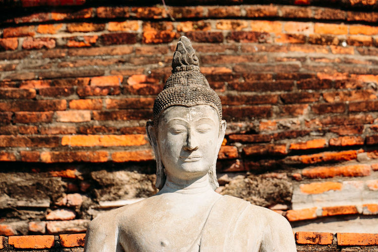 Statue of buddha against brick wall of building
