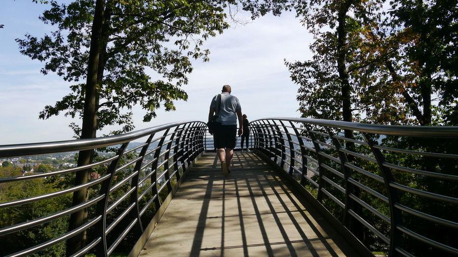 Rear view of man walking towards woman on footbridge