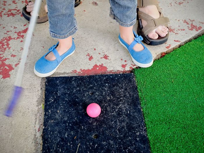 Low Section Of Adult And Child Playing Mini Golf