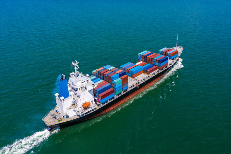 Containers ship import and export international businesses services by the sea aerial view