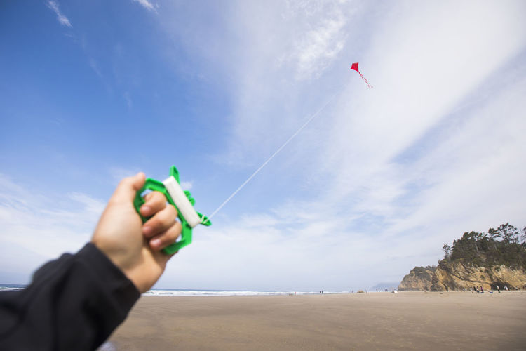 Person holding kite flying over beach against sky