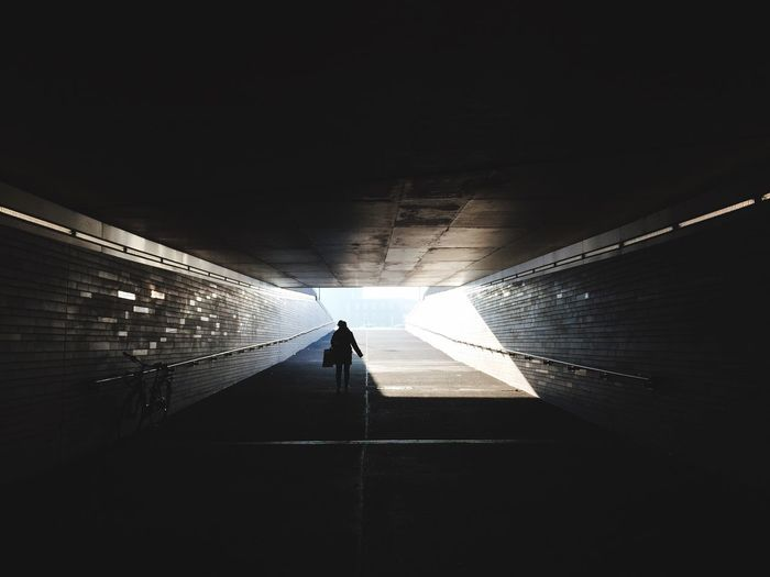 Rear view of silhouette man walking in tunnel