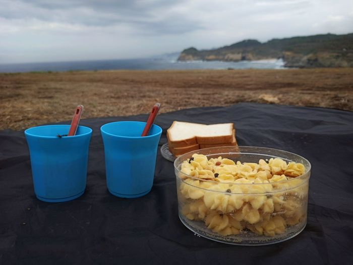 Close-up of food on table at beach against sky