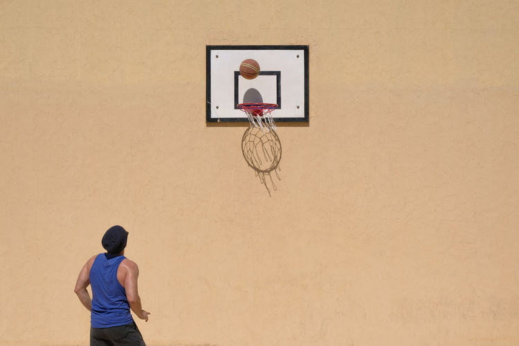 Rear view of man playing basketball against wall