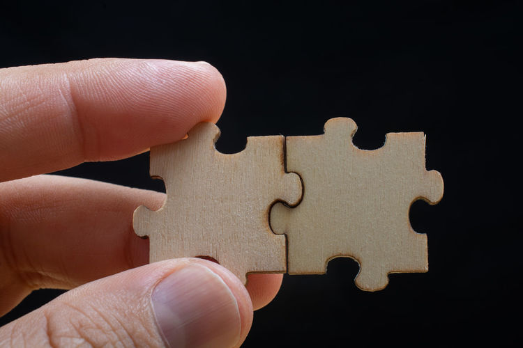 Close-up of hand holding jigsaw pieces against black background