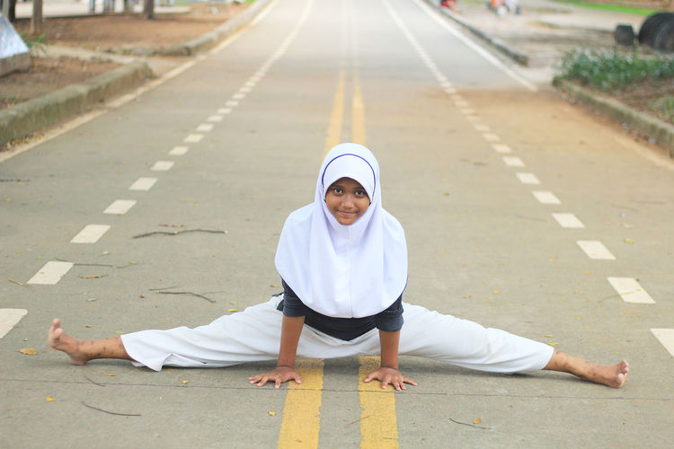 Portrait Of Girl In Hijab Doing Splits On Road