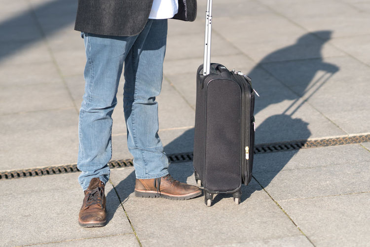 Low section of man with suitcase standing on tiled floor