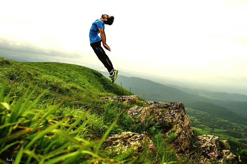 Full Length Of Man Levitating Over Mountain Against Sky