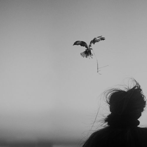 Low angle view of silhouette woman flying against clear sky
