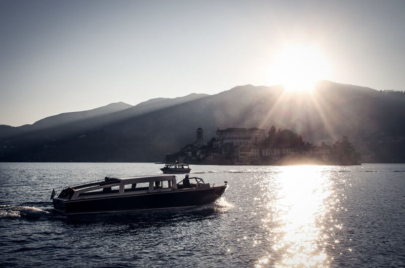 Laggo De Orta Beauty In Nature Boat Clear Sky Day Island Isola San Giulio Jet Boat Lake Mode Of Transport Mountain Nature Nautical Vessel Outdoors River Sailing Scenics Sky Sun Sunbeam Sunlight Sunset Transportation Water Waterfront