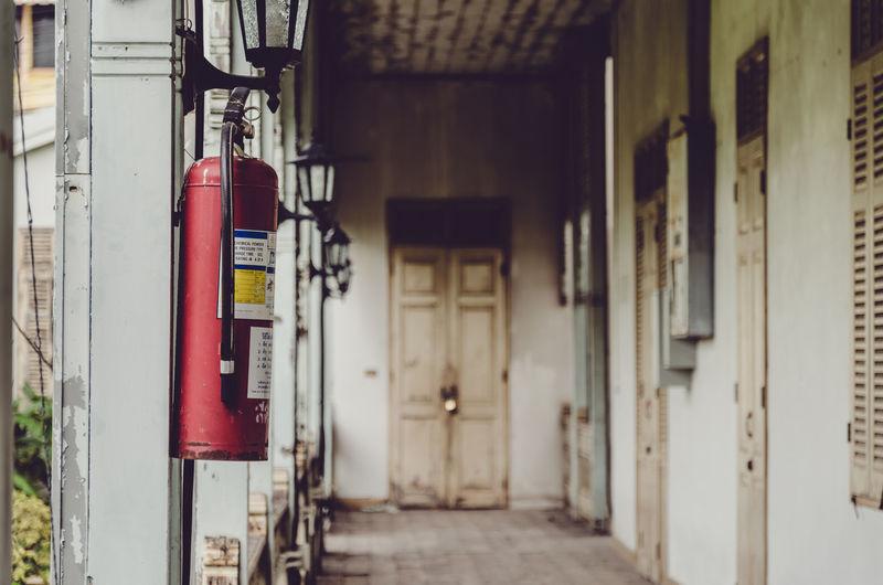 Fire extinguisher hanging in corridor of building