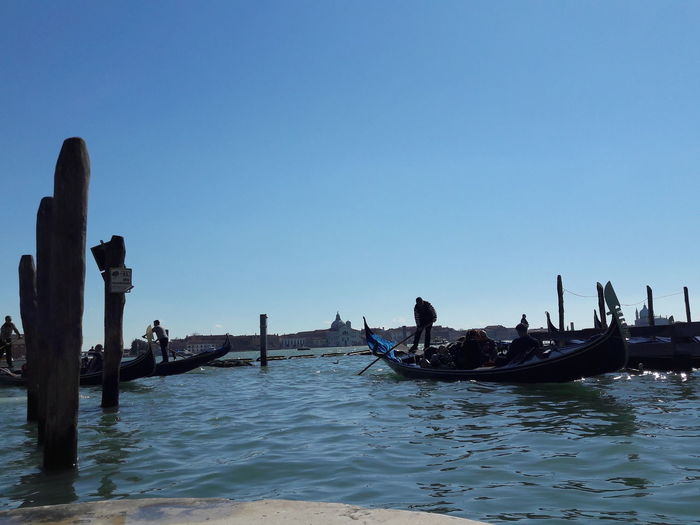 People enjoying in canal against clear blue sky