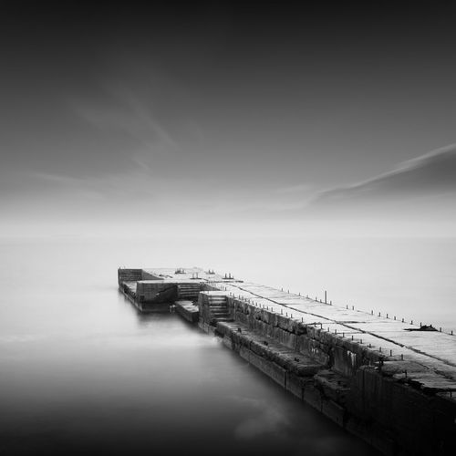 Pier amidst sea against cloudy sky during foggy weather