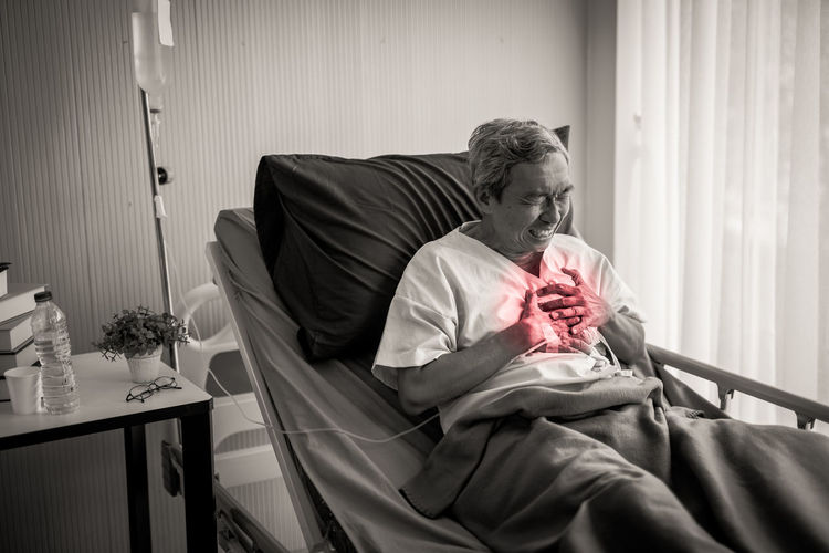 Senior Male Patient With Chest Pain On Bed In Hospital