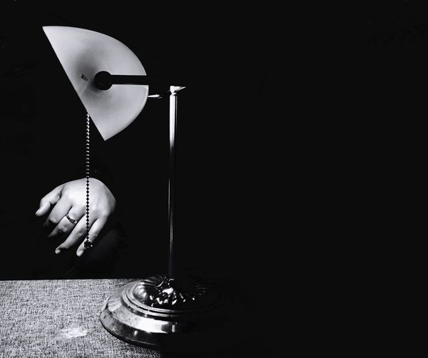 Cropped hand by illuminated lamp on table in darkroom