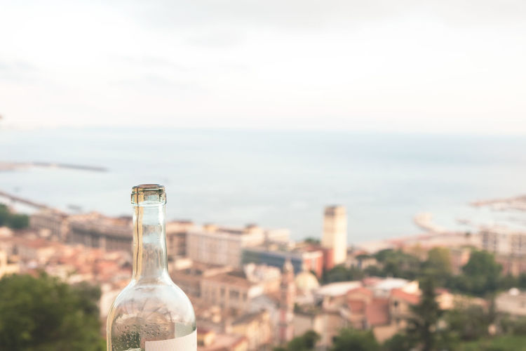 Close-up of wine bottle by sea against cityscape