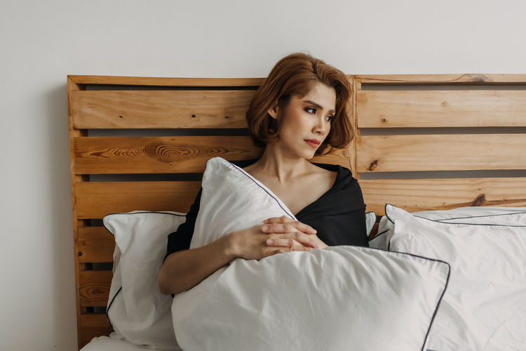 Young woman looking away while relaxing on bed at home
