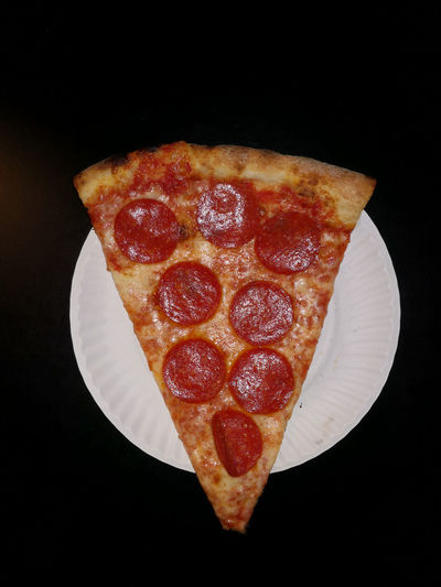 Close-up of pizza over black background
