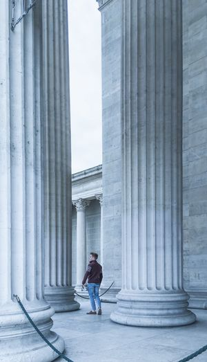 Man standing amidst columns of historic building