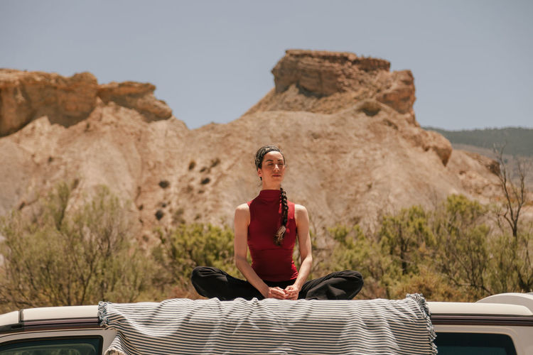 Low angle view of woman meditating while sitting on car roof