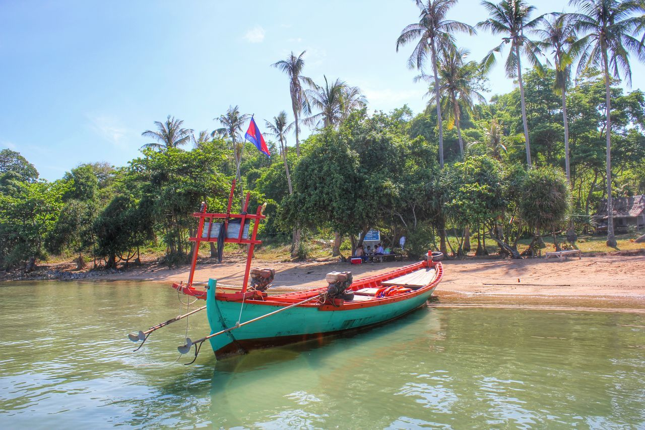 tree, day, flag, mode of transport, transportation, nautical vessel, water, nature, waterfront, patriotism, outdoors, beauty in nature, growth, moored, real people, longtail boat, sky