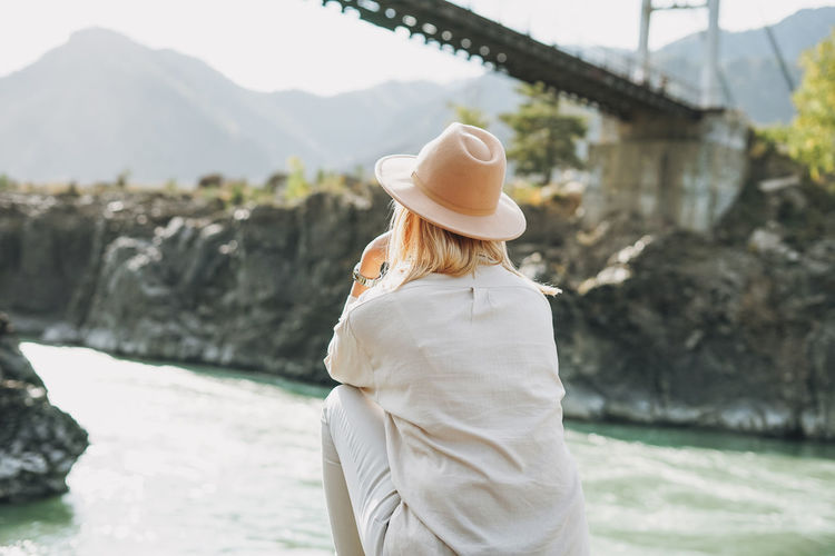 Young woman in felt hat from behind looking on horochowski bridge on katun river, altai mountains