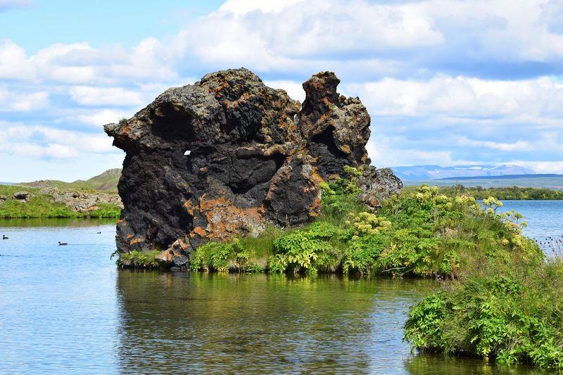 Rock in lake myvatn against cloudy sky