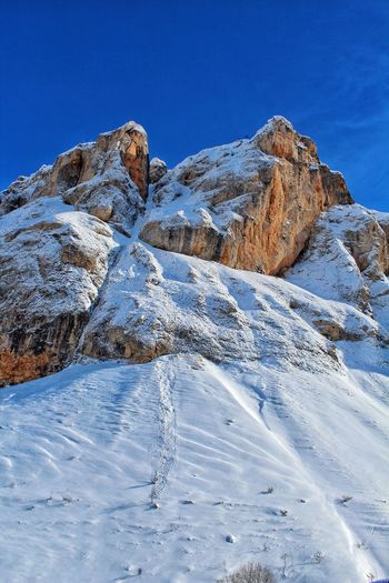Snow Mountain Blue Winter Cold Temperature Clear Sky Sky Landscape Rocky Mountains Tranquil Scene Rock Formation Arid Landscape Countryside Cliff Geology Snowcapped Mountain Rugged Rocky Coastline Rock - Object Physical Geography Calm Stack Rock Tranquility Eroded Mountain Range Horizon Over Water Natural Arch
