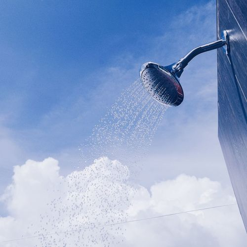 Low angle view of water falling from shower head against sky