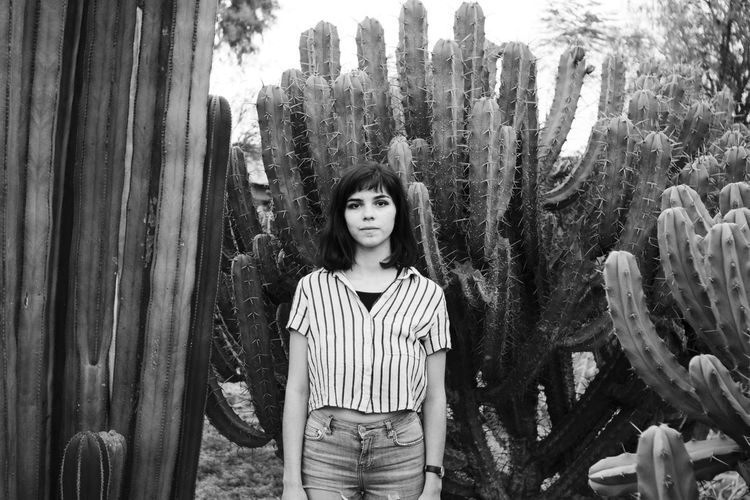 Portrait of young woman standing against cacti