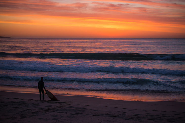 Silhouette surfer with skateboard at beach against sky during sunset