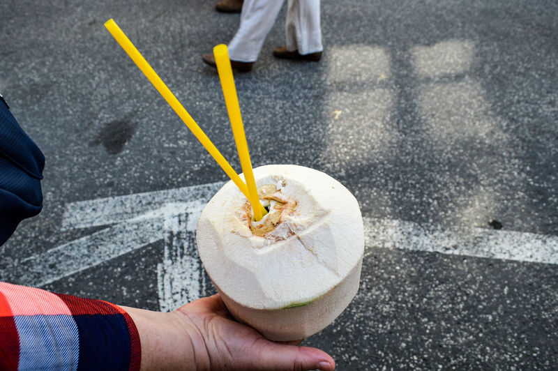Cropped image of hand holding coconut on street
