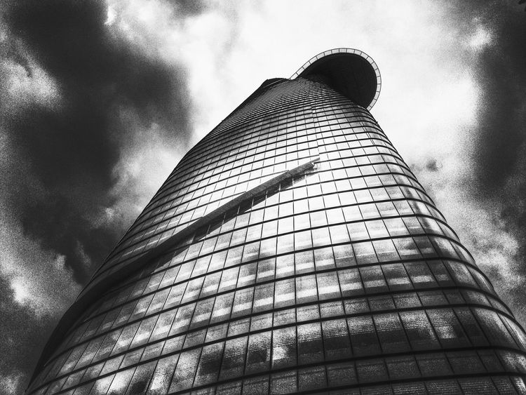 Lookingup at the Bitexco financial tower with the useless Helipad in Saigon Vietnam Hcmc Black And White Clouds And Sky