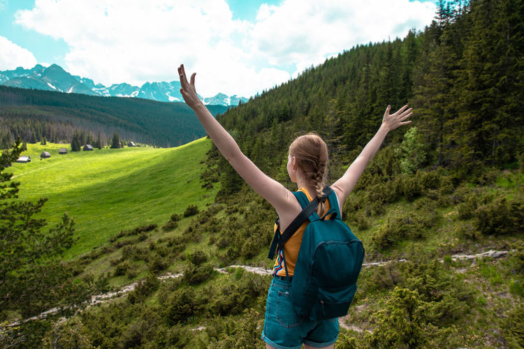 Woman tourist with hands standing cliff of rock. lifestyle travel adventure outdoor summer vacations