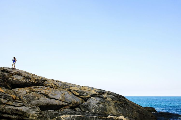 Woman Standing On Rock By Sea Against Clear Blue Sky
