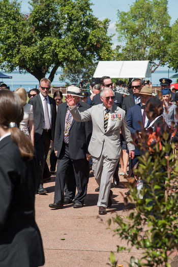 Darwin,Northern Territory,Australia-April 10,2018: Charles, Prince of Wales, waving to crowd while leaving after wreath laying ceremony at Bicentennial Park in Darwin, Australia Australia British Celebrity Darwin Famous Northern Territory Prince Of Wales Spectators Suit Waving Bicentennial Park Celebration Crowd Evening Memorial Event Men Prince Charles Royal Royalty Security Guard Sunglasses Sunlight Togetherness Tour Walking