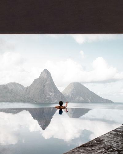 Rear view of man in infinite pool