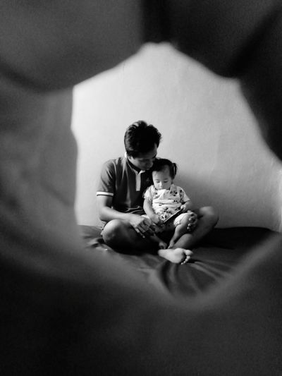 Father sitting with daughter seen through fingers