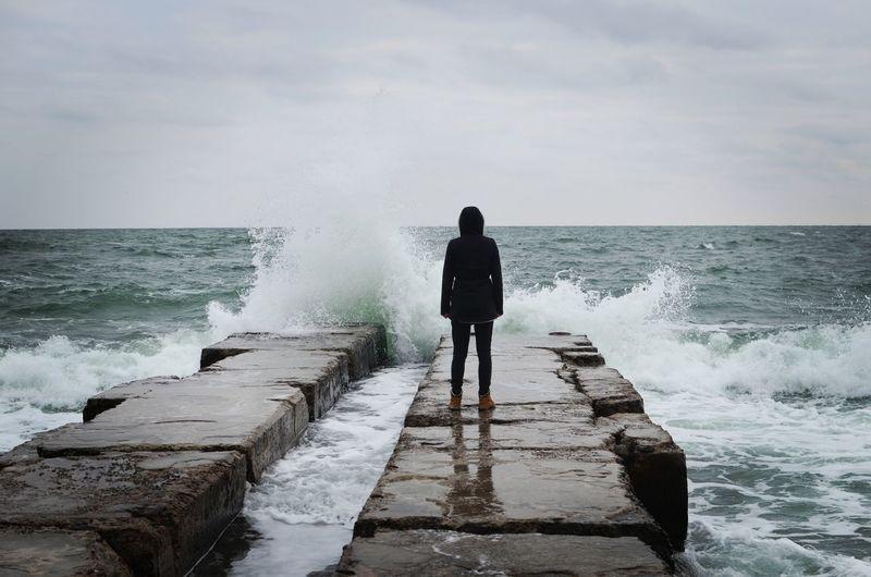 Rear View Of Woman Standing On Groyne In Sea Against Sky