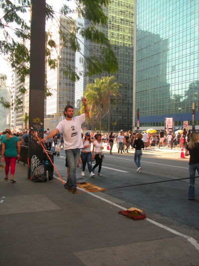 July 15, 2018 - On Sunday Avenida Paulista is closed off to traffic. This is the day when people take to the street to relax, exercise, walk, jog, ride bicycles, listen to music, have a snack and soak up the sun. In this photo, a man successfully walks a tightrope as part of the entertainment on Avenida Paulista. Avenida Paulista City Life Financial District  Susan A. Case Sabir The Architect - 2018 EyeEm Awards The Photojournalist - 2018 EyeEm Awards The Street Photographer - 2018 EyeEm Awards Unretouched Photography Building Exterior Built Structure City City Planning Downtown São Paulo Emotion Glass Skyscraper Group Of People Leisure Activity Positive Emotion Real People Street Sunny Day Tightrope Tightrope Walker Tightrope Walking Urban Landscape