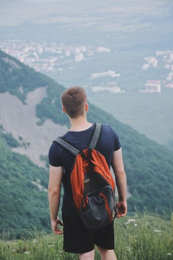 Rear View Of Man With Backpack Standing On Mountain