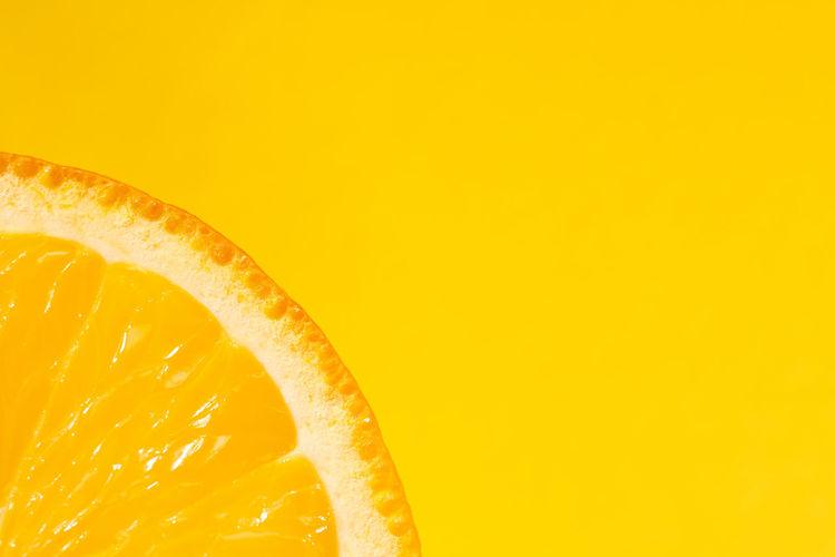 Close-up of orange fruit against yellow background