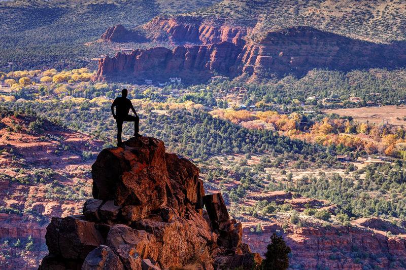 Silhouette people on rock