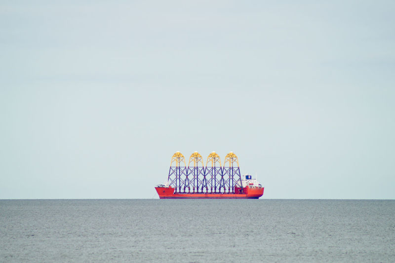 Container ship sailing on sea against clear sky