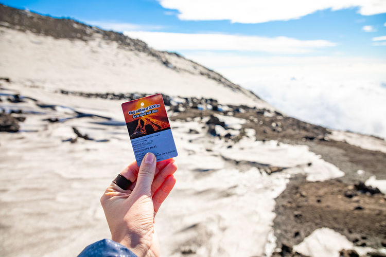 Etna Volcano Crater Mountain Winter Snow Sicily Italy Ash Ticket One Person Holding Real People Leisure Activity Day Human Body Part Nature Land Human Hand Lifestyles Beach Hand Sky Focus On Foreground Unrecognizable Person Personal Perspective Outdoors Scenics - Nature Body Part Finger